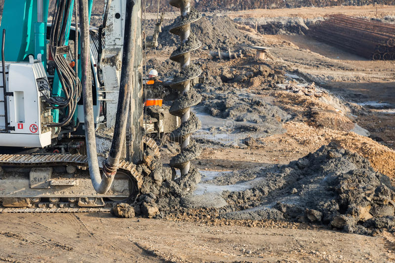 Drilling tractor installs concrete piles stock photo