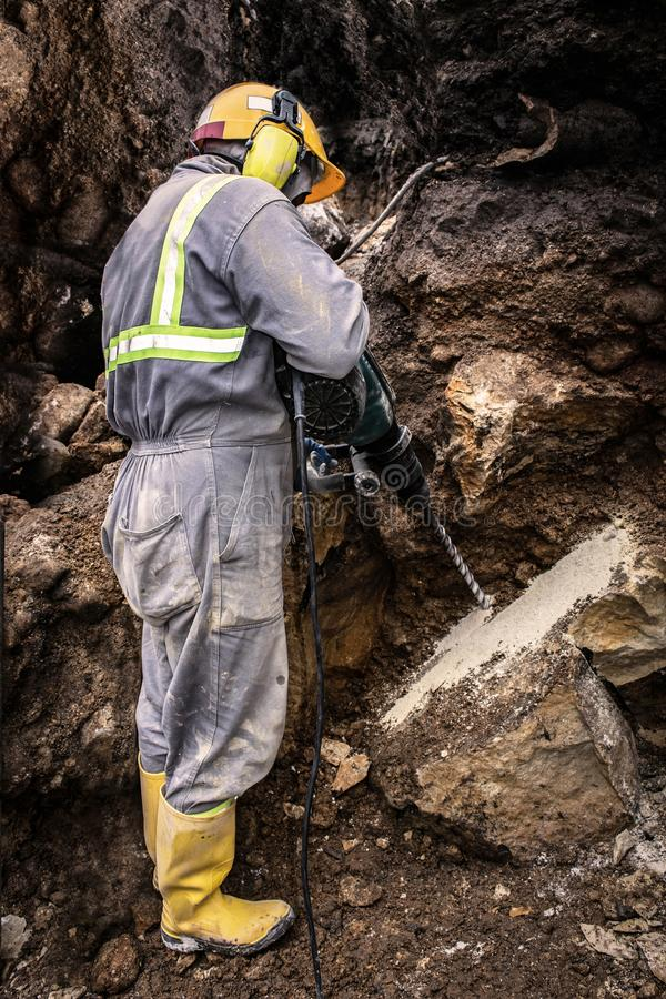 Drilling worker doing his job. Workerman with helmet and protective suit using drill-machine in an underground environment stock images
