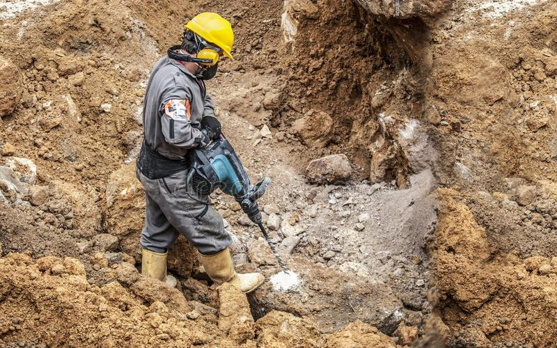 The drilling worker. Workerman with helmet and protective suit using drill-machine in an underground environment stock images