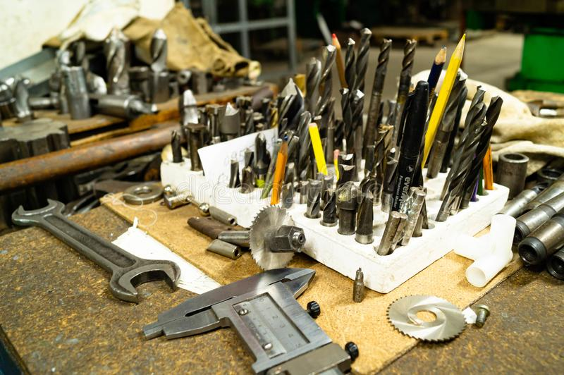 Drills, milling cutters and other metalworking tools on the table in the workshop. stock images