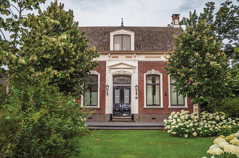 Charming brick rustic house with flowered garden and green lawn in a cloudy day at Drimmelen. stock photos