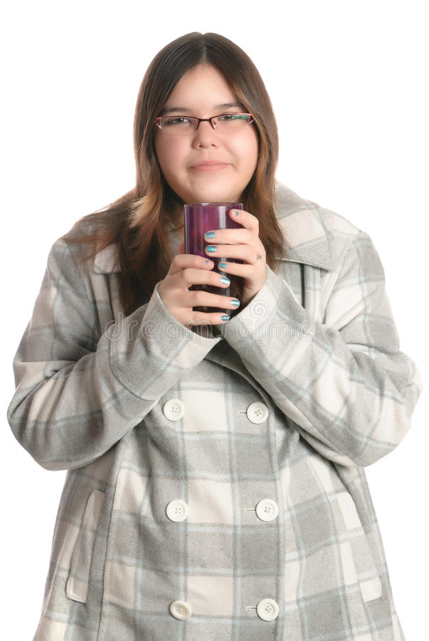 Drink. A smiling teenage girl is wearing a fall coat while holding a glass full of juice, isolated against a white background stock photo