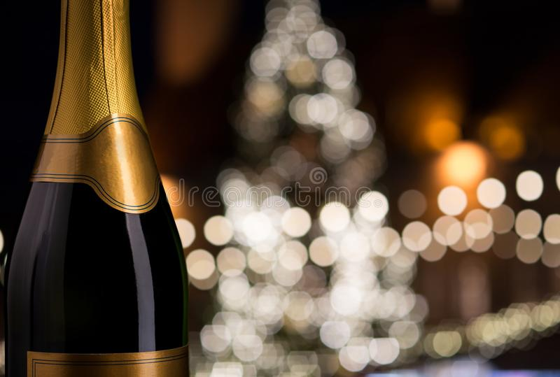 Close up of champagne bottle over christmas lights. Drink, alcohol and holidays concept - close up of bottle of champagne with blank golden label over christmas stock photo