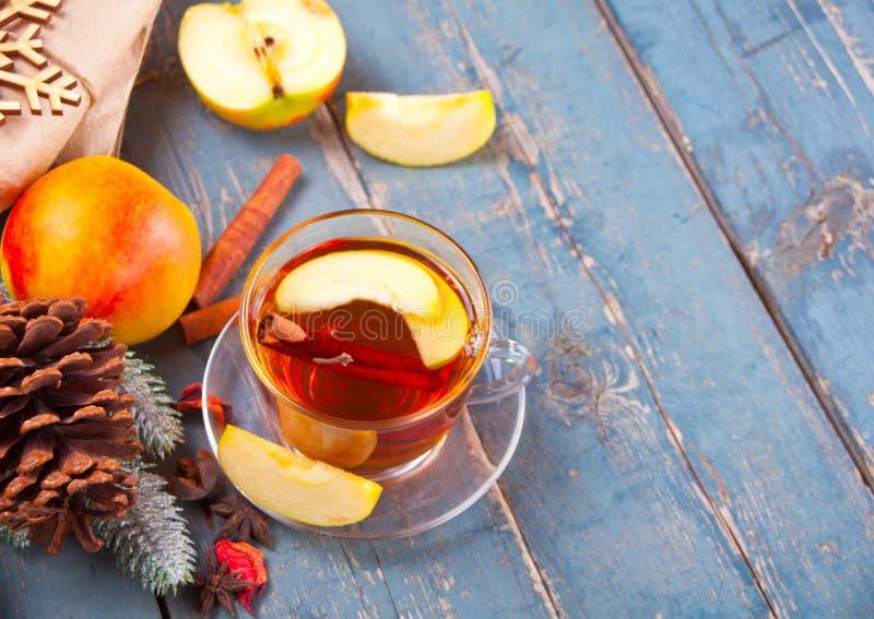 Drink av äpplete med den kanelbruna pinnen, stjärnaanis och kryddnejlikan Säsongsbetonad stansmaskin i kopp på träbakgrund arkivbild