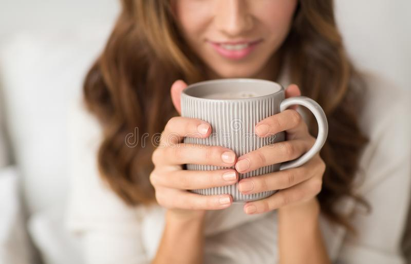 Close up of happy woman with cup of coffee at home royalty free stock photography