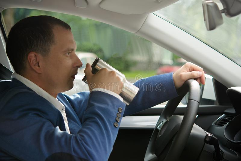 Drink coffee at the wheel of a car royalty free stock photography