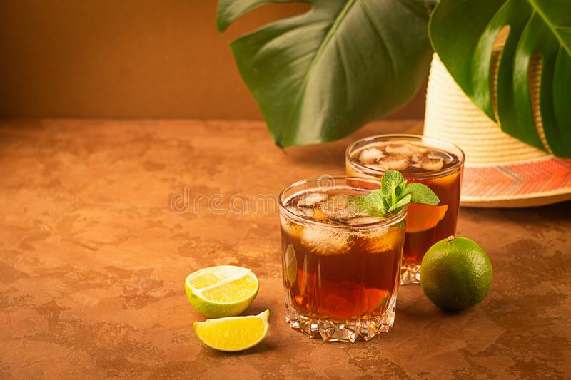 Drink cold tea with ice cubes and mint in two glass goblets a dark brown background. Alcoholic or non-alcoholic mahito. royalty free stock image