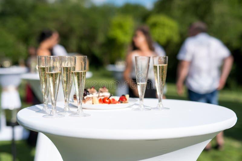 Drink di benvenuto, vista dei vetri riempiti di champagne su una tavola in un giardino immagini stock libere da diritti