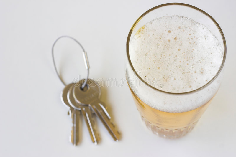 Drink driving. Beer and set of keys isolated on a white background royalty free stock image