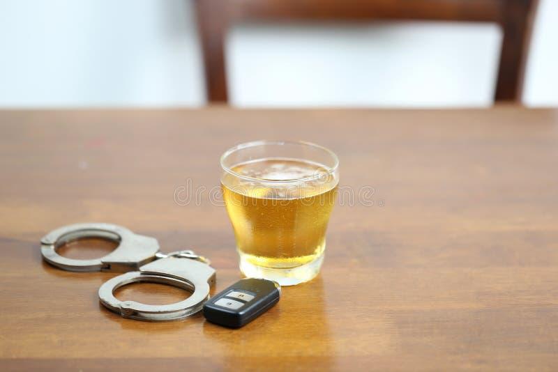 Drink en drijf concept, Glazen bier met autosleutels en geen sluiting op de lijst stock afbeelding