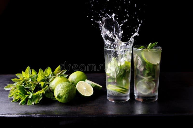 Drink för alkohol för coctail Mojito för traditionell strand uppfriskande i exponeringsglas med färgstänk, vatten för stångförber royaltyfri foto