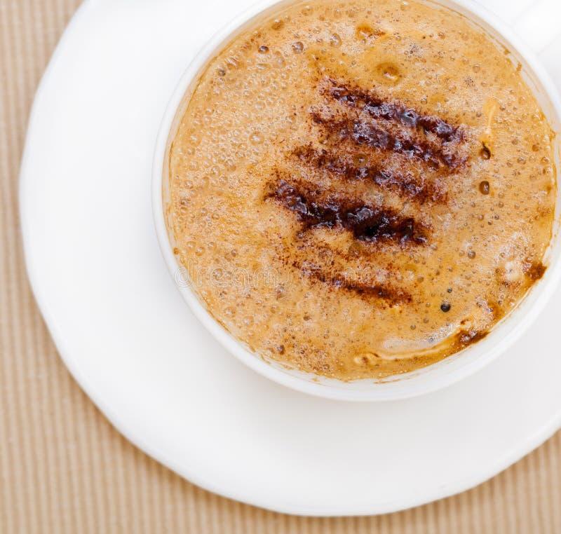 Drink för dryck för vit koppcoffe varm med fradga på brun bakgrund royaltyfri fotografi