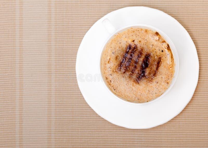 Drink för dryck för vit koppcoffe varm med fradga på brun bakgrund arkivfoto