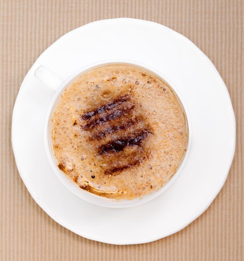 Drink för dryck för vit koppcoffe varm med fradga på brun bakgrund royaltyfri foto