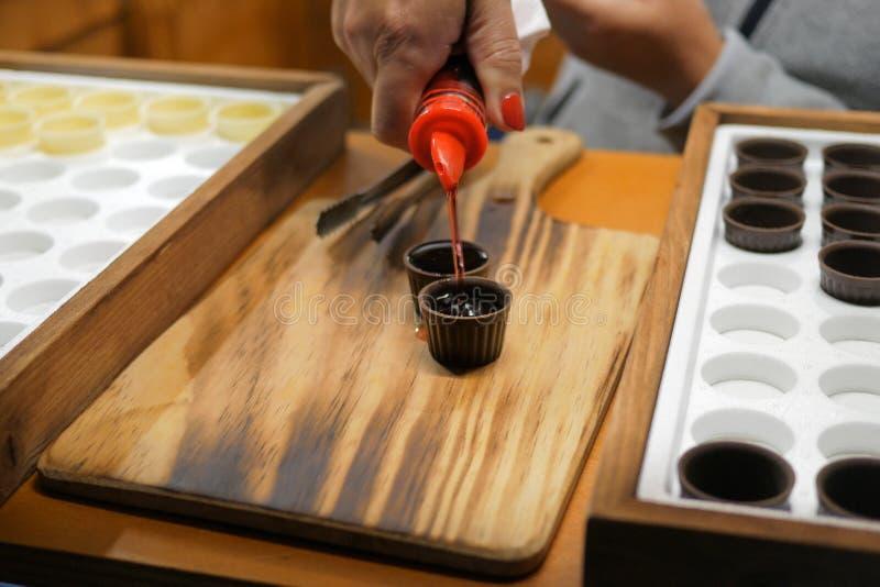 Drink för hällande Ginja/Ginjinha körsbärsröd likör in i chokladkoppar på träbakgrund Traditionell portugisisk drink royaltyfria foton