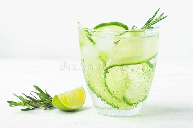 Drink från saftig limefruktkvist för ny gurka av rosmarin i en exponeringsglasbägare på en vit bakgrund F?rnyande detox f?r somma fotografering för bildbyråer