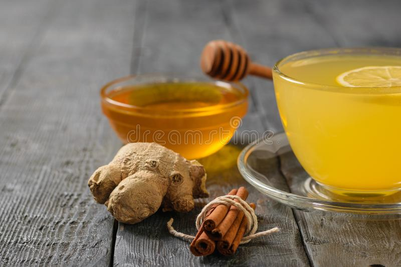 A drink of ginger, honey and citrus fruits to strengthen the immune system on the black wooden table royalty free stock image