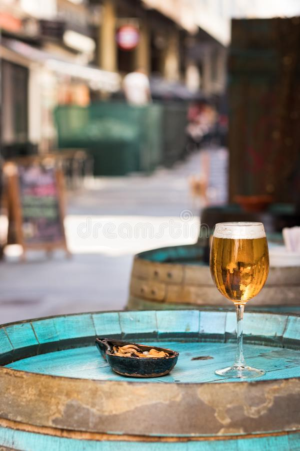 A glass with beer and mussels on a wooden wine barrel as a table. A drink glass with beer next to a plate with mussels without shell placed on a wooden barrel as stock image