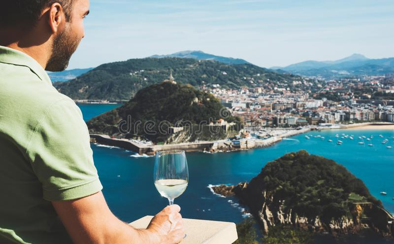 Drink glass white wine in male hands holidays looks top view city coast yacht from observation deck, romantic lonely tourist man. Toast with alcohol panoramic royalty free stock photo
