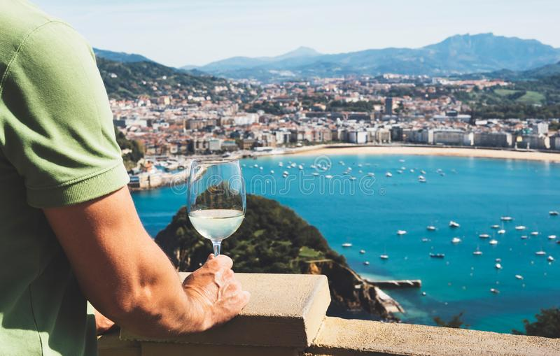 Drink glass white wine in male hands holidays looks top view city coast yacht from observation deck, romantic tourist man toast wi. Th alcohol panoramic royalty free stock image