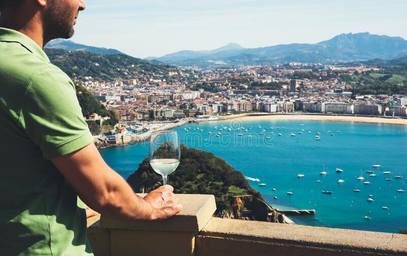 Drink glass white wine in male hands holidays looks top view city coast yacht from observation deck, romantic tourist man toast. With alcohol panoramic royalty free stock image