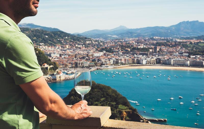 Drink glass white wine in male hands holidays looks top view city coast yacht from observation deck, tourist man toast with alco. Hol panoramic cityscape stock photo