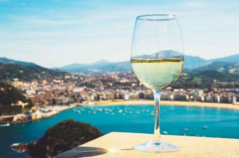 Drink glass white wine standing on background blue sea top view city coast yacht from observation deck, romantic lonely toast. With alcohol panoramic cityscape royalty free stock image