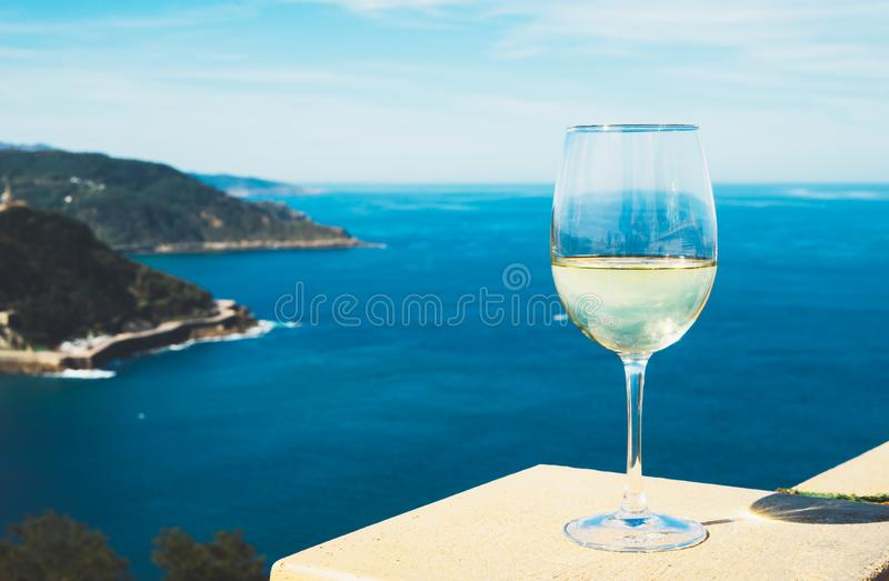 Drink glass white wine standing on background blue sea top view city coast yacht from observation deck, romantic lonely toast stock images