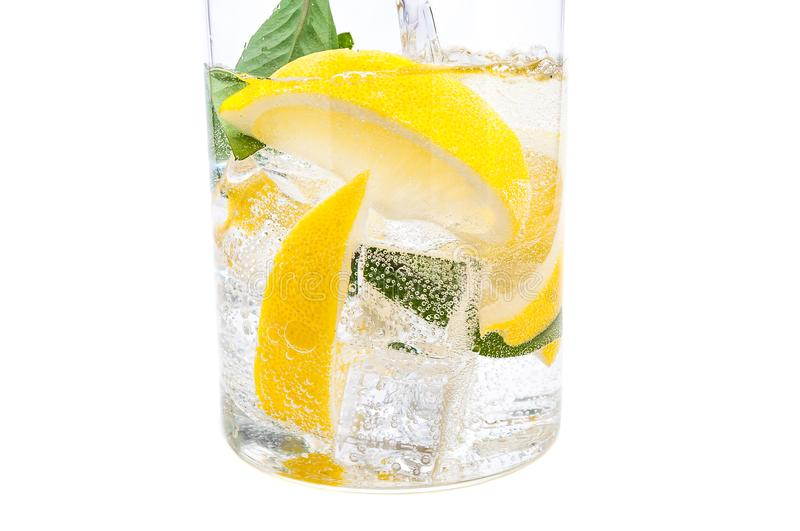 Drink of ice, the lobules of fresh juicy yellow lemon and crystal clear water in a glass. stock image