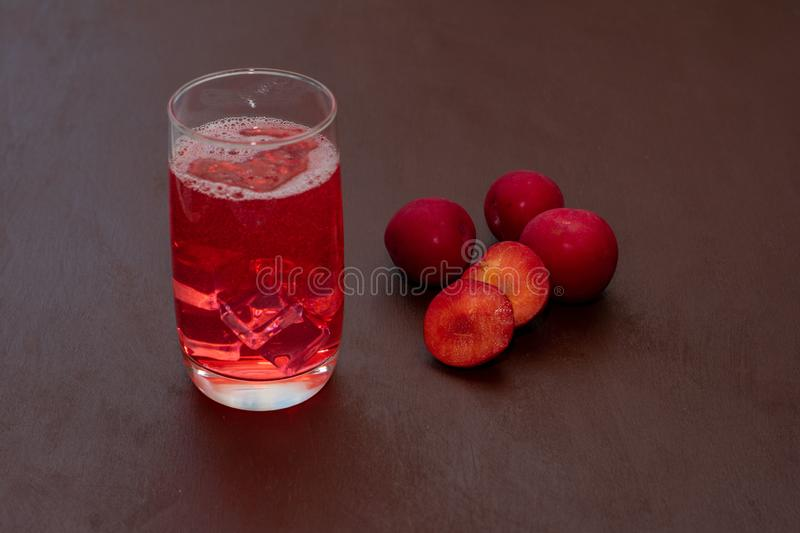 Drink with ice plum on a dark background. Fresh plum cocktail. Fresh summer cocktail with plum and ice cubes. A glass of plum soda stock photo