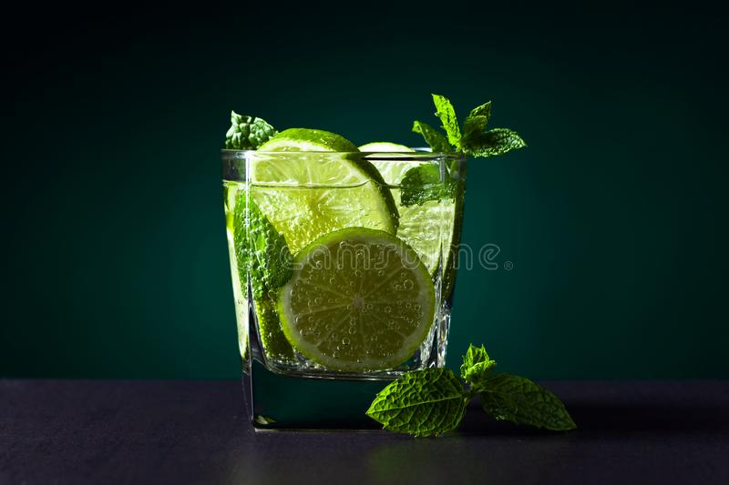 Drink with lime . Drink with lime , ice and peppermint on black table in bar stock image