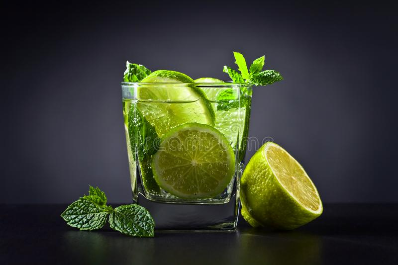 Drink with lime . Drink with lime , ice and peppermint on black table in bar royalty free stock image