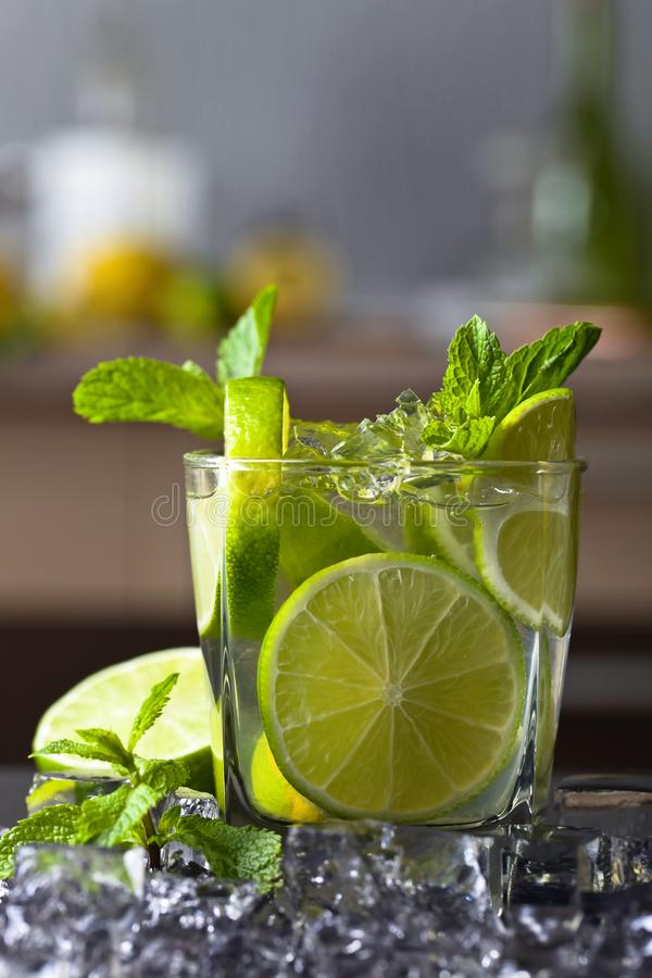 Drink with lime . Drink with lime and peppermint on a black in bar royalty free stock image