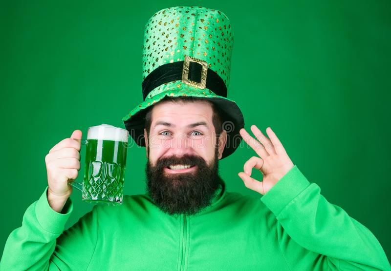 This drink is on me. Celebrating saint patricks day in beer pub. Hipster in green leprechaun wear holding beer mug. Irish man gesturing ok to green beer stock photo