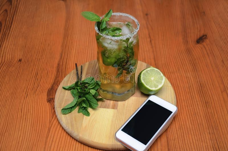 Drink with mint and lime. Drink mojito, mojito with mint, ice and lime and phone, on a wooden table, macro photography stock photography