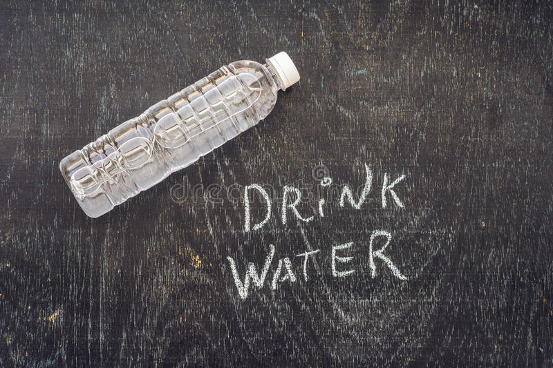Drink more water - hydration reminder - handwriting on On a chalk board.  stock photo