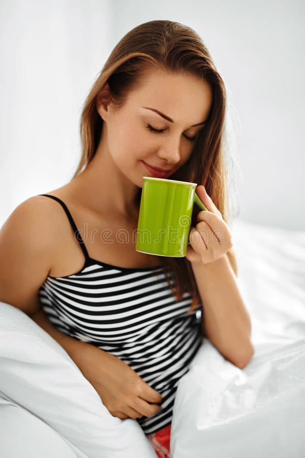 Drink Morning Tea. Woman Drinking Beverage In Bed. Healthy Lifestyle. Morning Drink. Closeup Beautiful Happy Smiling Woman Enjoying Cup Of Coffee Or Tea In royalty free stock photo