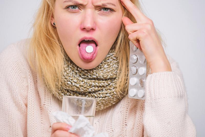 Drink plenty of fluids. Breaking fever concept. Girl take medicine to break fever. Headache and fever remedies. Woman. Sick person hold glass water and tablets stock image
