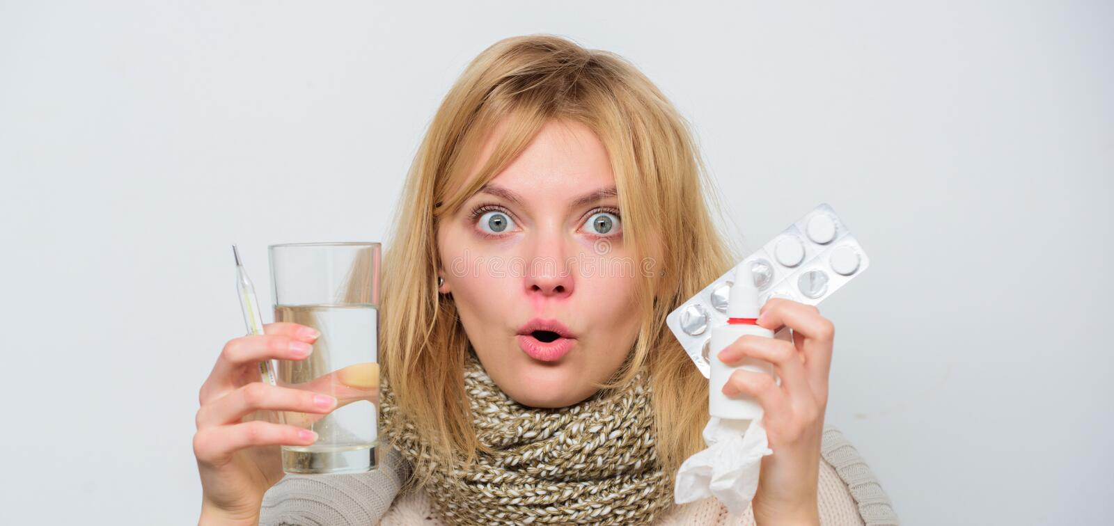 Drink plenty of fluids. Girl take medicine to break fever. Breaking fever concept. Headache and fever remedies. Woman. Sick person hold glass water and tablets stock image