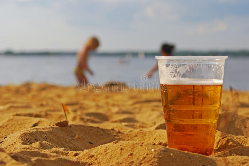 Drink Responsibly. Think of your loved ones. Beer in Foreground with Children playing in background royalty free stock photos