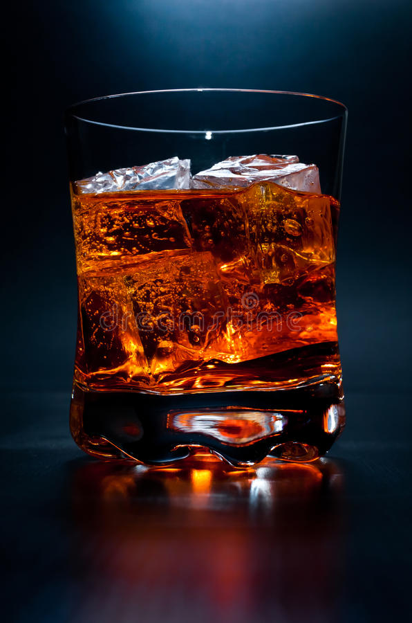 Drink on the rocks. A glass filled with an alcoholic drink and ice cubes on dark background stock image
