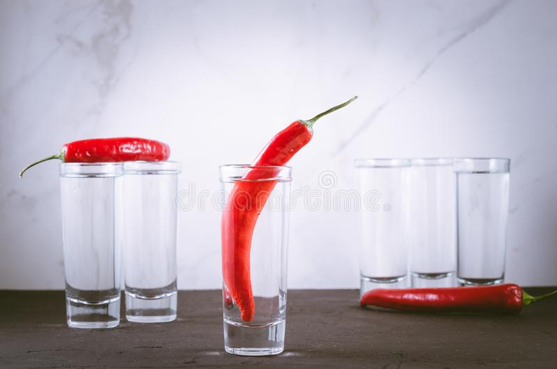 Drink set with shots of vodka and red pepper/Drink set with shots of vodka and red pepper on a white marble background. Selective. Focus stock images