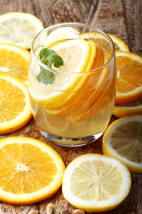 Drink and stack of citrus fruits slices. Oranges and lemons. On wooden plate royalty free stock photo