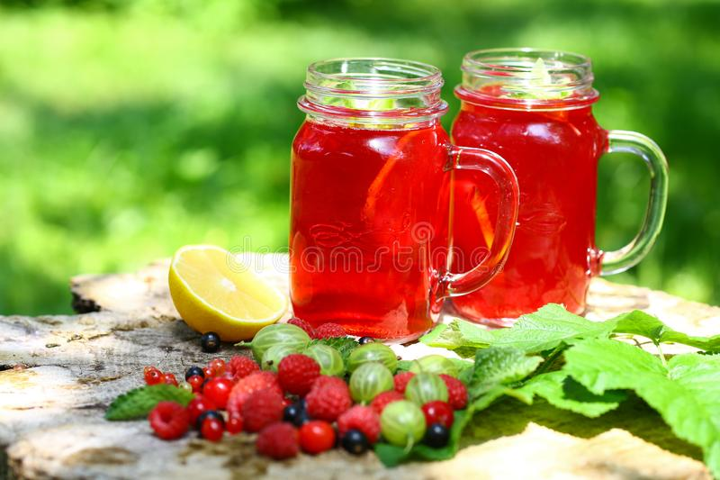Drink Summer from Mix Berries Decorated with Green Mint. Compote in in a glass jar with a straw. Old Background outdoors. Superfoo royalty free stock images