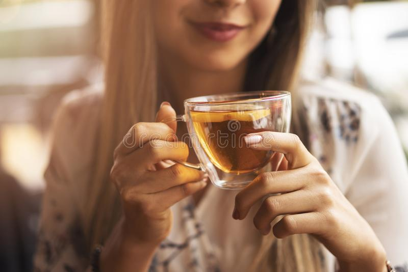 Drink Tea relax cosy photo with blurred background. Female hands holding mug of hot Tea in morning. Young woman relaxing tea cup.  royalty free stock images