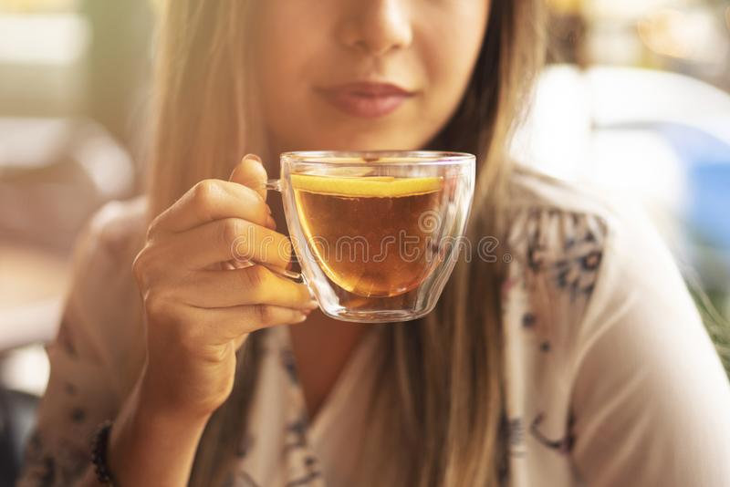 Drink Tea relax cosy photo with blurred background. Female hands holding mug of hot Tea in morning. Young woman relaxing tea cup royalty free stock photo