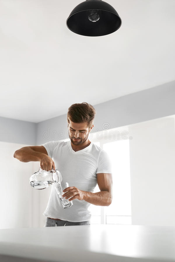 Drink Water. Close Up Man Pouring Water Into Glass. Hydration. Drink Water. Handsome Smiling Young Man Pouring Fresh Pure Water From Pitcher Into A Glass In stock images