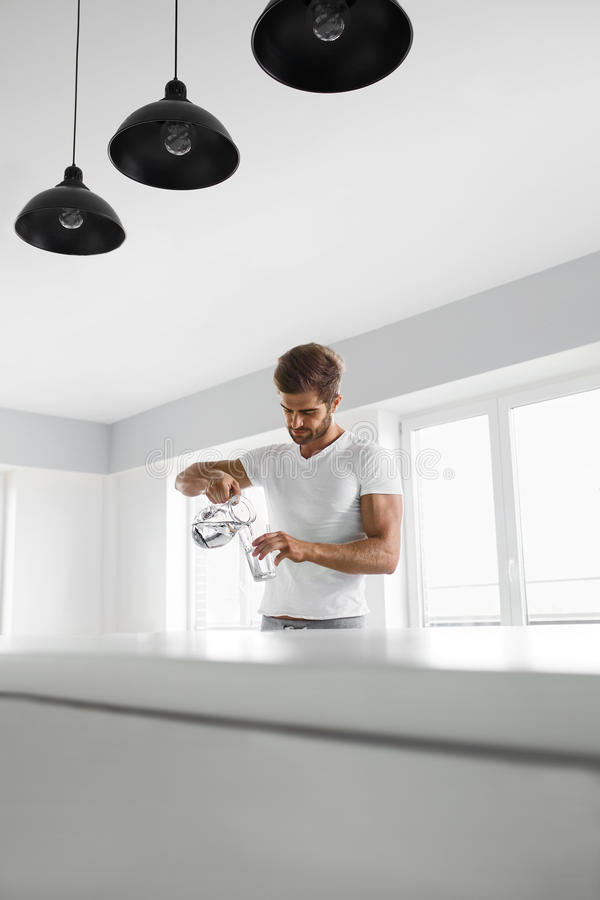 Drink Water. Close Up Man Pouring Water Into Glass. Hydration. Drink Water. Handsome Smiling Young Man Pouring Fresh Pure Water From Pitcher Into A Glass In royalty free stock photography