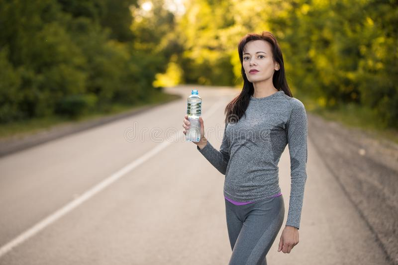 Drink water while jogging. girl holding a bottle of water. stock photo