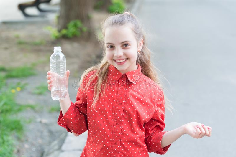 Drink water while walk. Teach kids about body hydration. Healthy habits. Healthy and hydrated. Girl care about health. And water balance. Girl cute kid hold stock photos